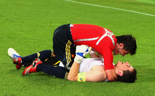 Casillas on ground and Villa on his knees above him.