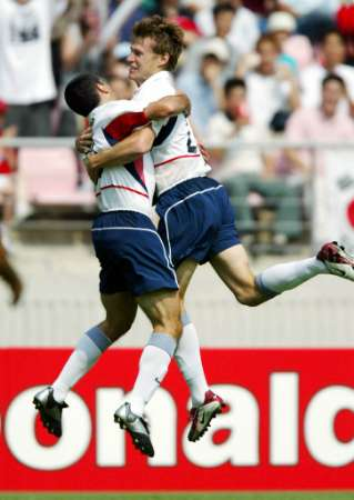Brian McBride leaps into Claudio Reyna's arms mid-air.